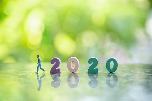 Zakończenie kolorowa drewniana liczba 2020 na ziemi up z biegacz miniaturową postacią bieg lewa strona i bokeh liścia zielona natura.
