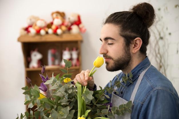 Zakończenie kwiaciarnia mężczyzna wącha tulipanowego kwiatu w bukiecie