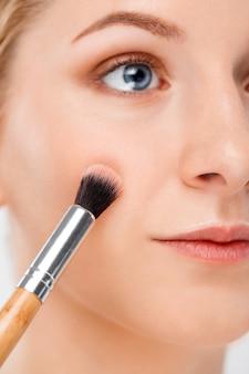 Zakończenie ładna kobieta stawia makeup z muśnięciem