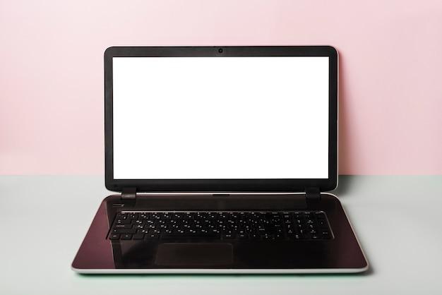 Zakończenie laptop z bielu ekranem na biurku przeciw różowemu tłu