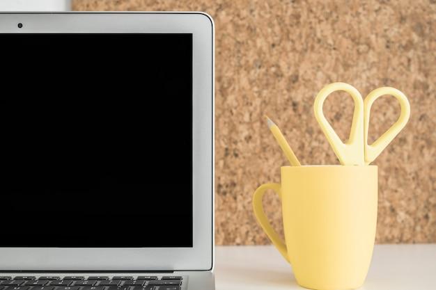 Zakończenie Laptopu Ekran Z Nożycowym I Ołówkiem W żółtej Filiżance Na Biurku Darmowe Zdjęcia