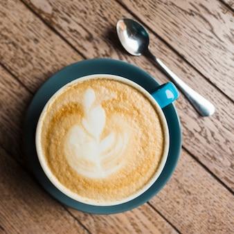Zakończenie latte kawa z kreatywnie latte sztuką na drewnianym textured tle