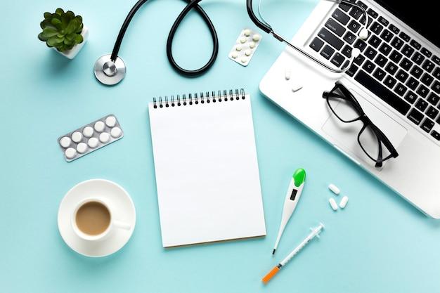 Zakończenie lekarka stół z medycznymi rzeczami i filiżanką kawy
