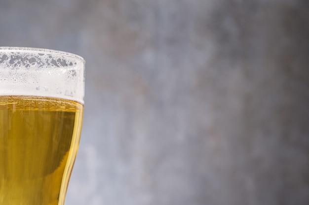 Zakończenie lekki piwo w szkle na szarości ścianie