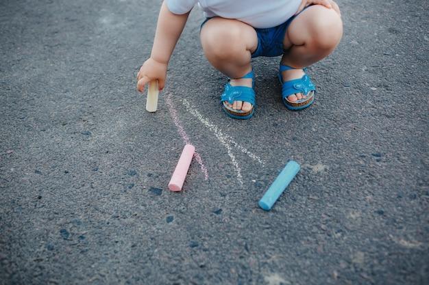 Zakończenie mała dziewczynka rysunek z pisze kredą na chodniczku up