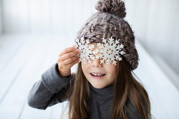 Zakończenie mała dziewczynka zakrywa jej twarz z płatkami śniegu