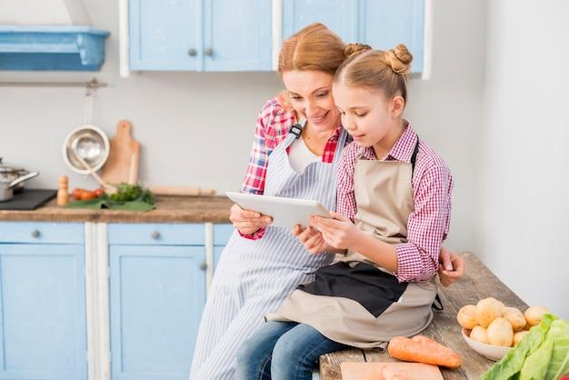 Zakończenie matka i córka patrzeje cyfrową pastylkę w kuchni