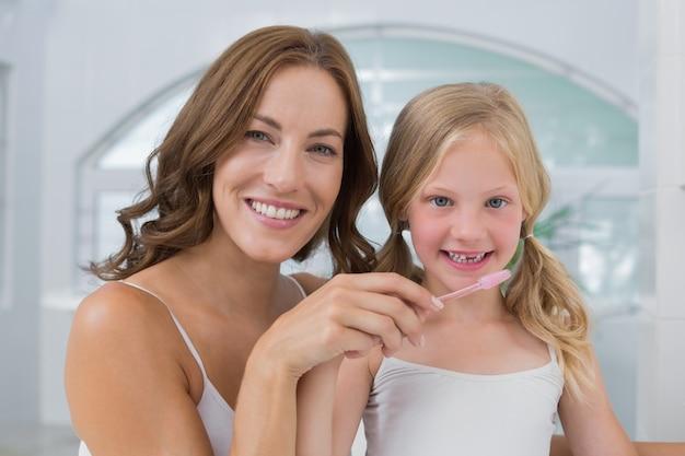 Zakończenie matka z córką szczotkuje zęby