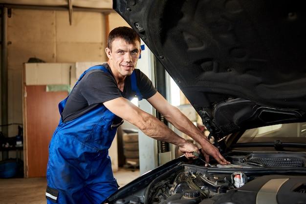 Zakończenie mechanik naprawia samochód w jego remontowym sklepie