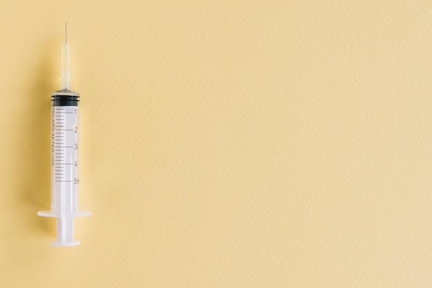 Zakończenie medyczna strzykawka na żółtym textured tle