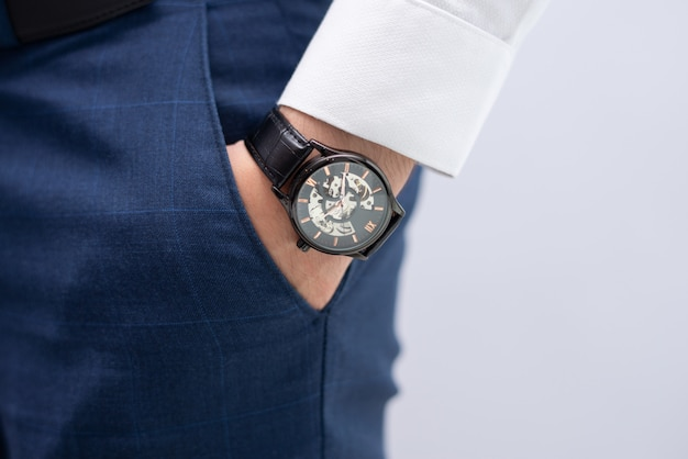 Zakończenie męska ręka w kieszeni z nowożytnym eleganckim wristwatch