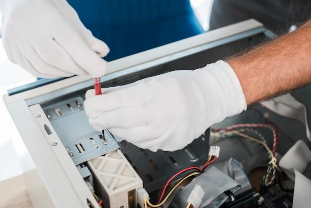 Zakończenie męska technik ręka jest ubranym rękawiczki naprawia komputer