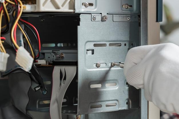 Zakończenie męska technik ręka jest ubranym rękawiczki załatwia śrubę w komputerowej szczelinie