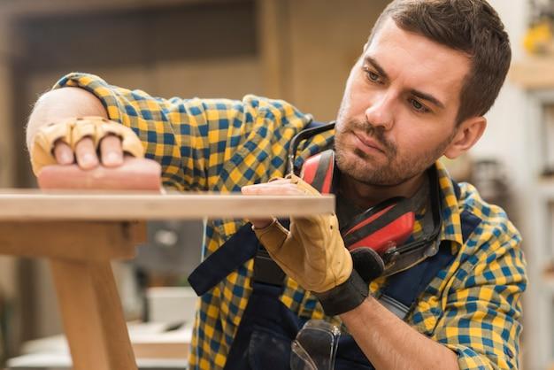 Zakończenie męski cieśla naciera piaska papier na drewnianej powierzchni