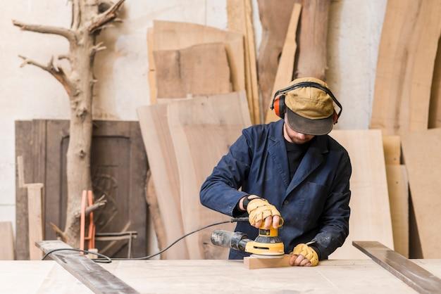 Zakończenie męski cieśla używa elektrycznego sander na drewnie