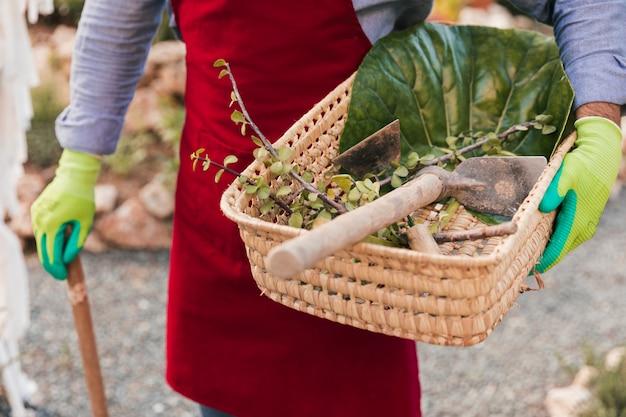 Zakończenie męski ogrodnik trzyma ogrodniczych narzędzia i zbierał liście w koszu