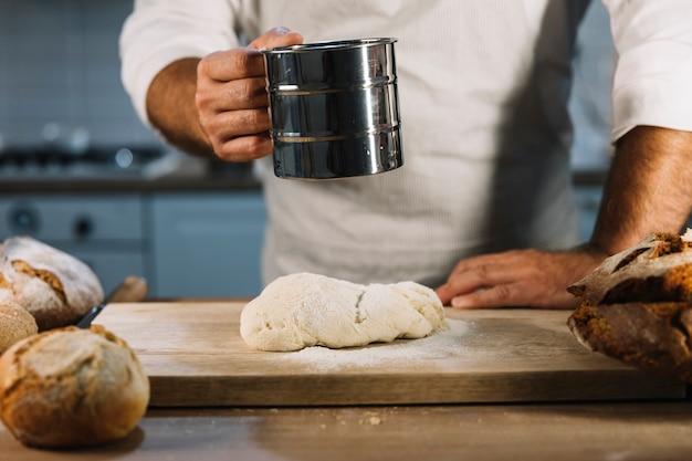 Zakończenie męski piekarz przesiewanie pszeniczną mąkę przez stalowego odsiewacza nad ugniata ciasto