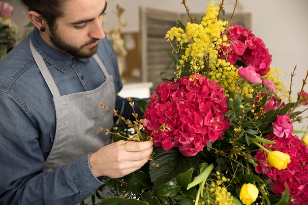 Zakończenie męski układanie kwiaty w bukiecie