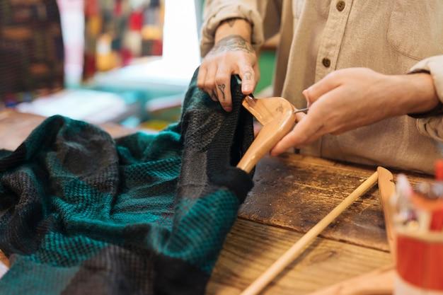 Zakończenie męski właściciel układa ubrania na wieszaku