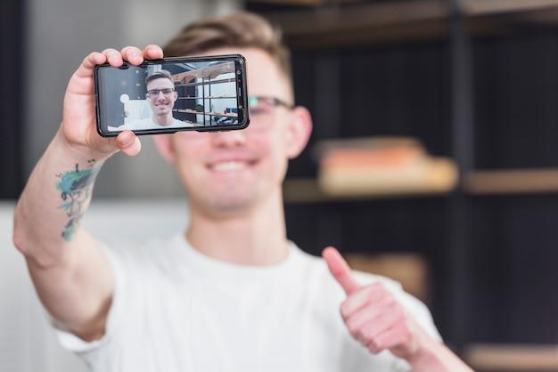 Zakończenie mężczyzna bierze selfie na telefonie komórkowym pokazuje kciuk up podpisuje