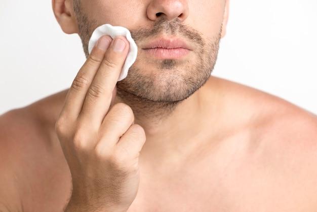 Zakończenie mężczyzna cleaning twarz z bawełnianym ochraniaczem
