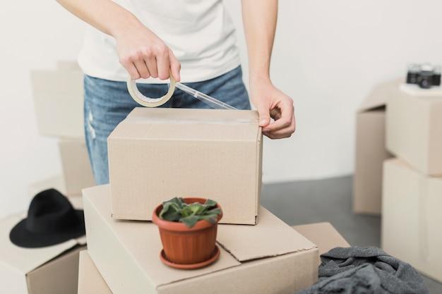 Zakończenie mężczyzna kładzenia wiolonczeli taśma na pudełku