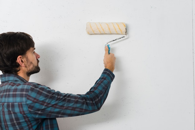 Zakończenie mężczyzna maluje ścianę z farba rolownikiem