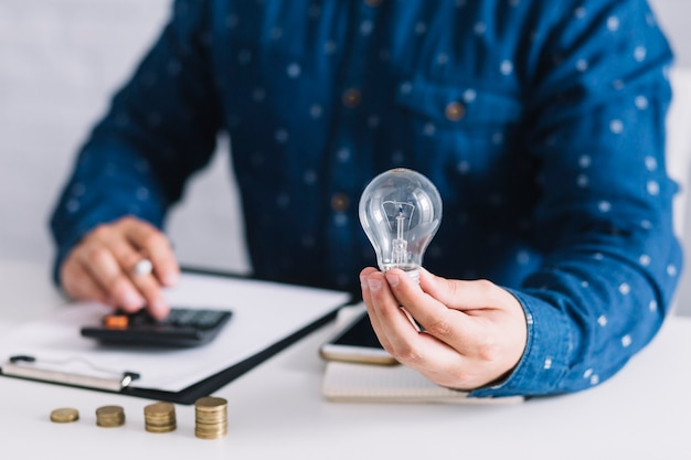 Zakończenie mężczyzna mienia lightbulb używać kalkulatora przy miejscem pracy