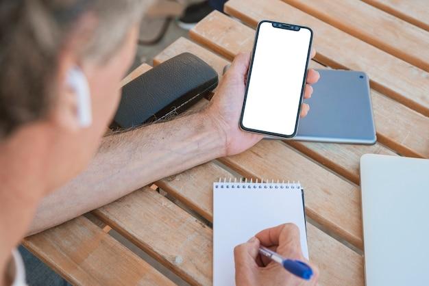 Zakończenie mężczyzna mienia smartphone writing na ślimakowatym notepad z piórem