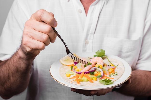 Zakończenie mężczyzna mienia talerz z zdrowym jedzeniem