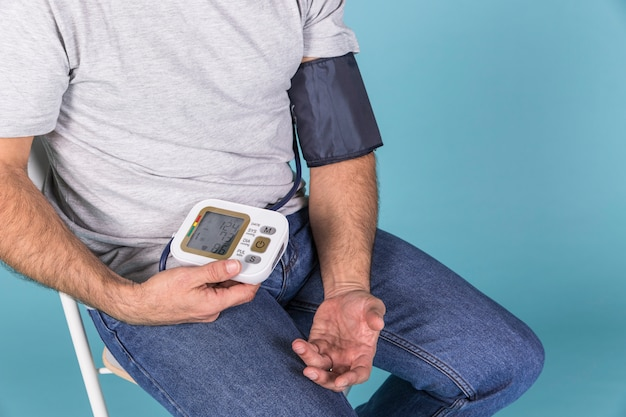Zakończenie mężczyzna obsiadanie na krześle sprawdza ciśnienie krwi na elektrycznym tonometer