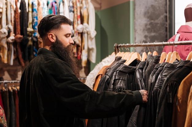 Zakończenie mężczyzna patrzeje skórzaną kurtkę na poręczu w odzieżowym sklepie