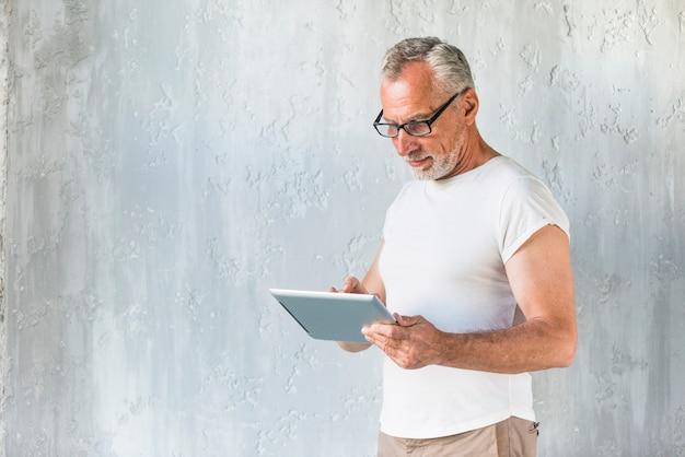 Zakończenie mężczyzna pozycja przed betonową ścianą używać cyfrową pastylkę