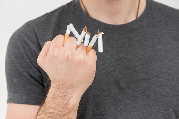 Zakończenie mężczyzna ręka pokazuje łamającego papieros w ręce