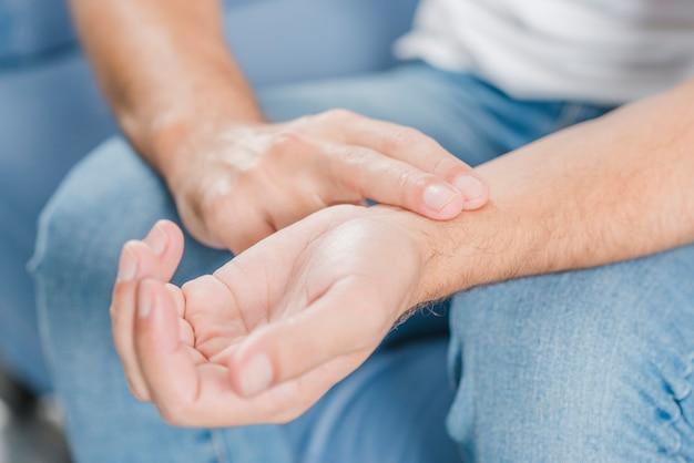 Zakończenie mężczyzna ręka sprawdza puls