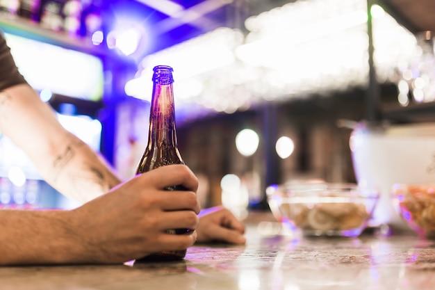 Zakończenie mężczyzna ręka trzyma piwną butelkę w barze