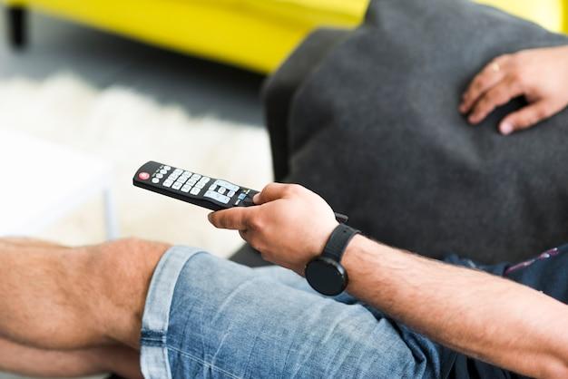 Zakończenie mężczyzna ręka trzyma telewizyjnego pilot do tv