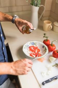 Zakończenie mężczyzna ręka ubiera sałatki z oliwa z oliwek w kuchni
