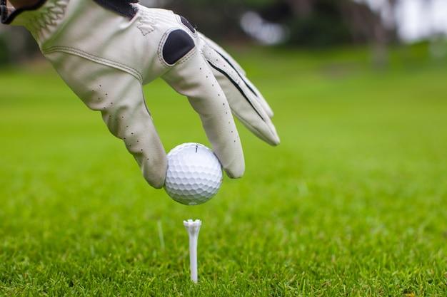 Zakończenie mężczyzna ręki chwyta piłka golfowa z trójnikiem na kursie