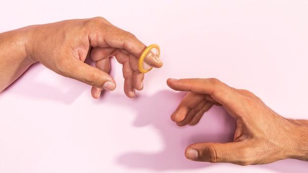 Zakończenie mężczyzna ręki z przejrzystym kondomem