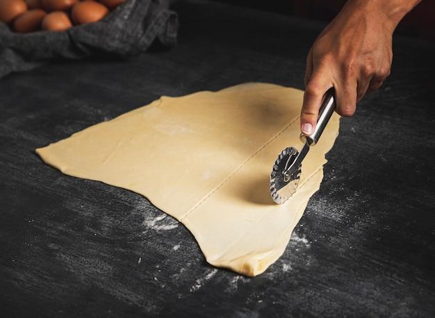 Zakończenie mężczyzna tnący ciasto z krajaczem do pizzy