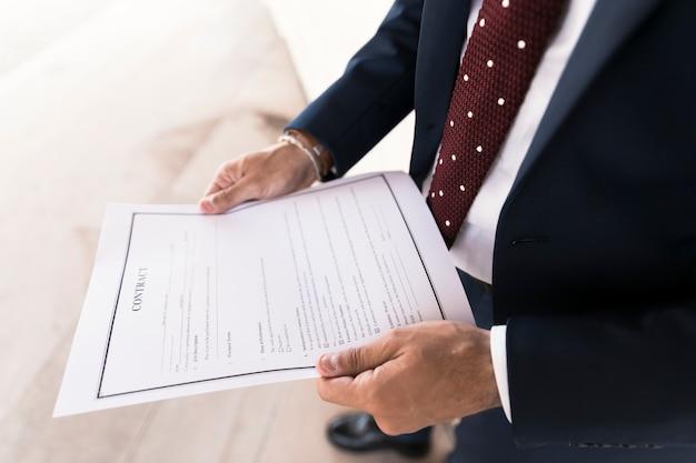 Zakończenie mężczyzna trzyma kontrakt w kostiumu