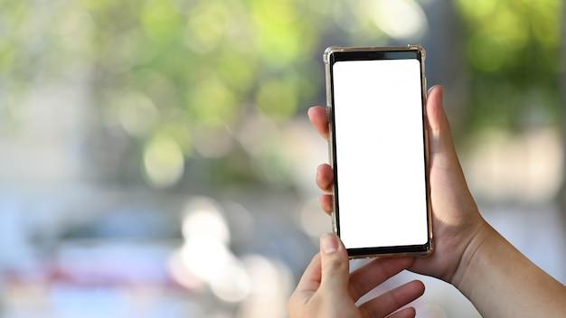 Zakończenie mężczyzna trzyma mobilnego mądrze telefon przy natury bokeh zamazanym