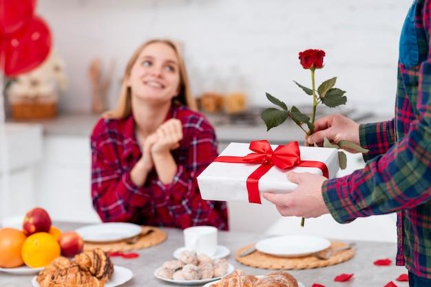 Zakończenie mężczyzna zaskakująca kobieta z różą i prezentem