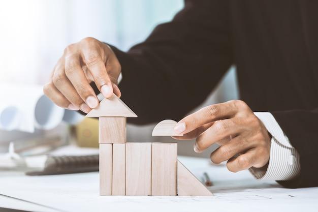 Zakończenie midsection biznesmen robi domu modelowi z drewnianymi blokami na budowa planie