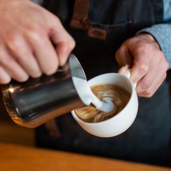 Zakończenie mleko nalewa w filiżance kawy