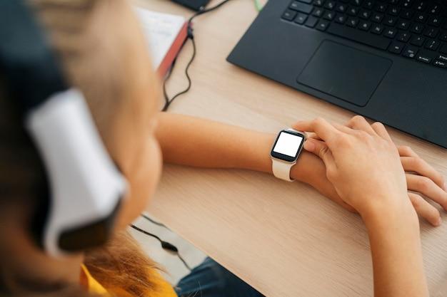 Zakończenie młoda dziewczyna sprawdza jej smartwatch
