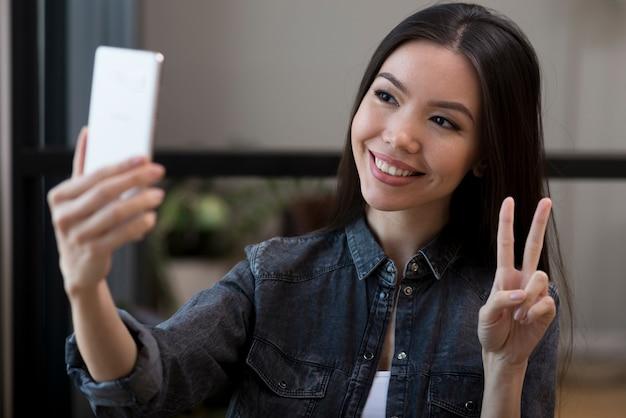 Zakończenie młoda kobieta bierze selfie z jej telefonem