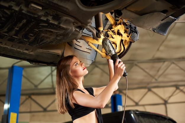 Zakończenie młoda kobieta z lampionem w jej ręce sprawdza samochód na hydraulicznym dźwignięciu w samochodowym remontowym sklepie