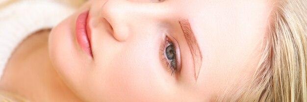 Zakończenie młoda powabna kobieta kłaść z malującym kształtem dla brwi. blondynka na spotkaniu z kosmetologami. koncepcja permanentnego makijażu i salon kosmetyczny wellness